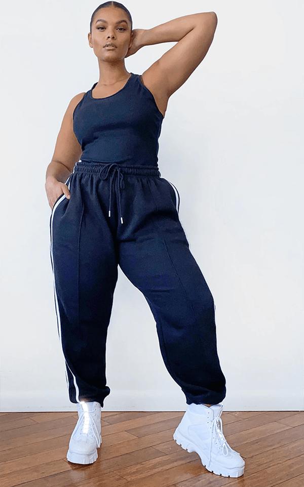 A plus-size model wearing black striped sweatpants.