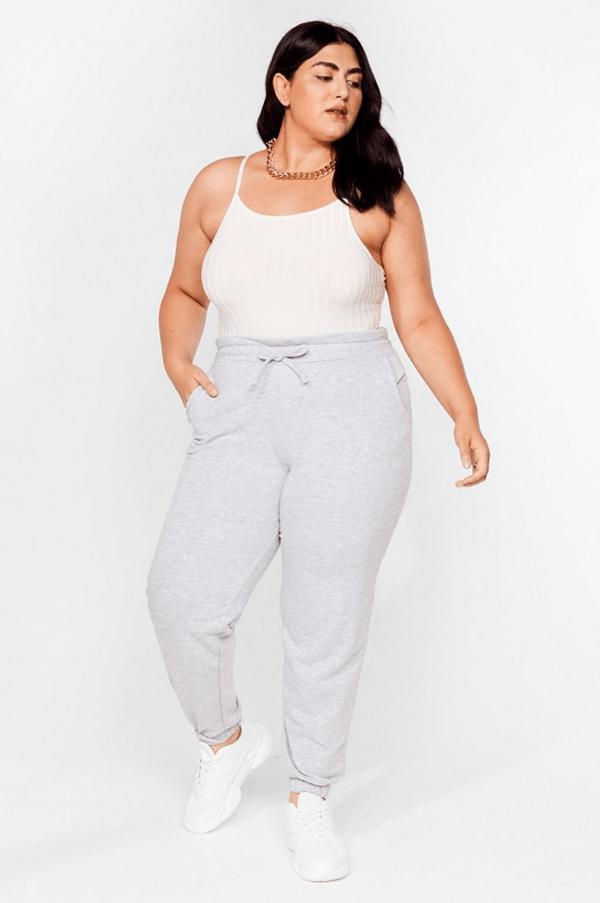 A plus-size model wearing gray sweatpants.