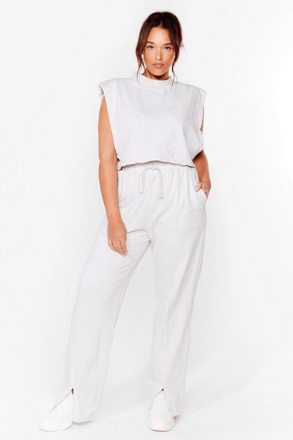 A plus-size model wearing white sweatpants.