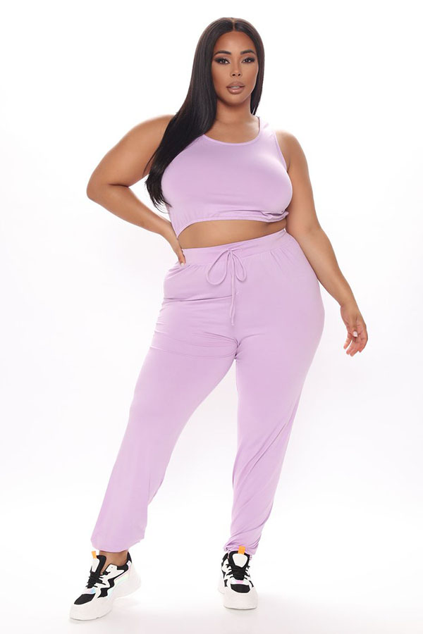 A plus-size model wearing pink sweatpants.