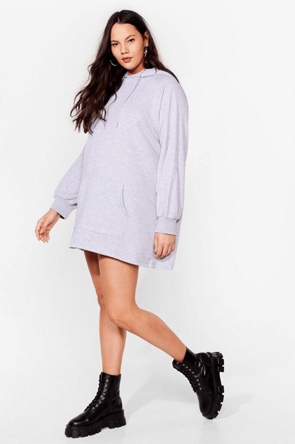 A plus-size model wearing a gray sweatshirt dress.