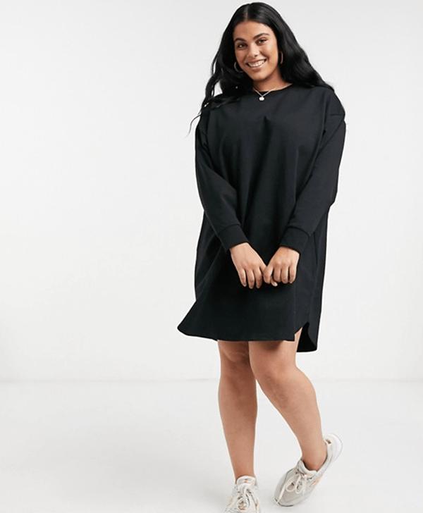 A plus-size model wearing a black sweatshirt dress.