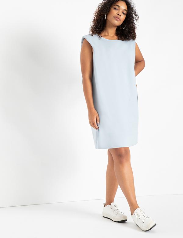 A plus-size model wearing a sleeveless gray sweatshirt dress.