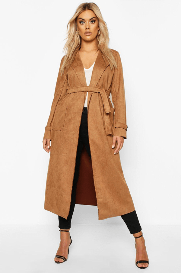 A plus-size model wearing a tan suede trench coat.