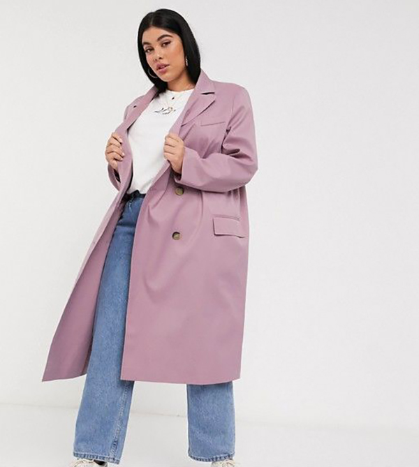 A plus-size model wearing a mauve trench coat.
