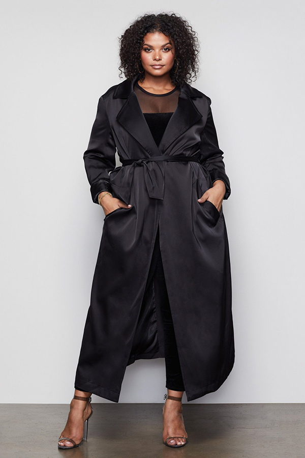 A plus-size model wearing a black satin trench coat.