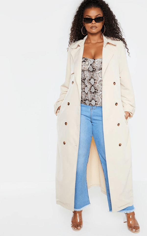 A plus-size model wearing an off-white trench coat.