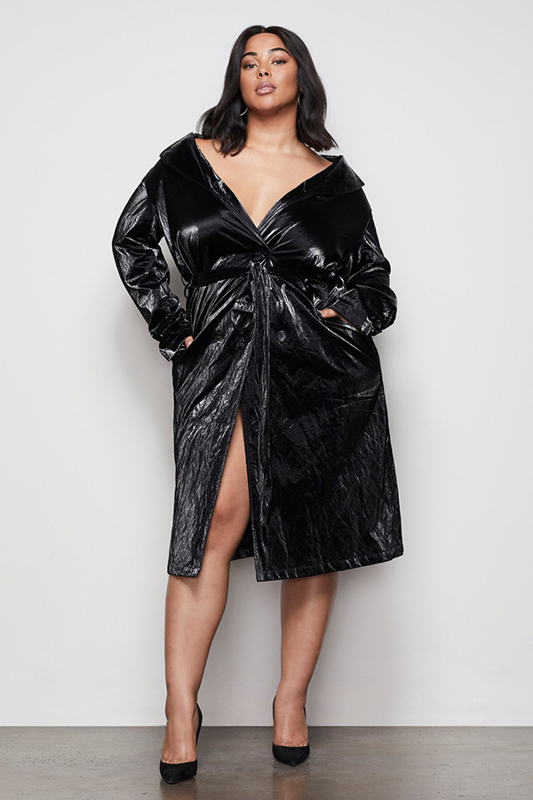 A plus-size model wearing a charcoal velvet trench coat.