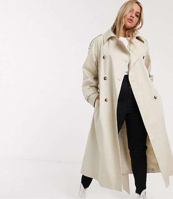 A plus-size model wearing a beige trench coat.