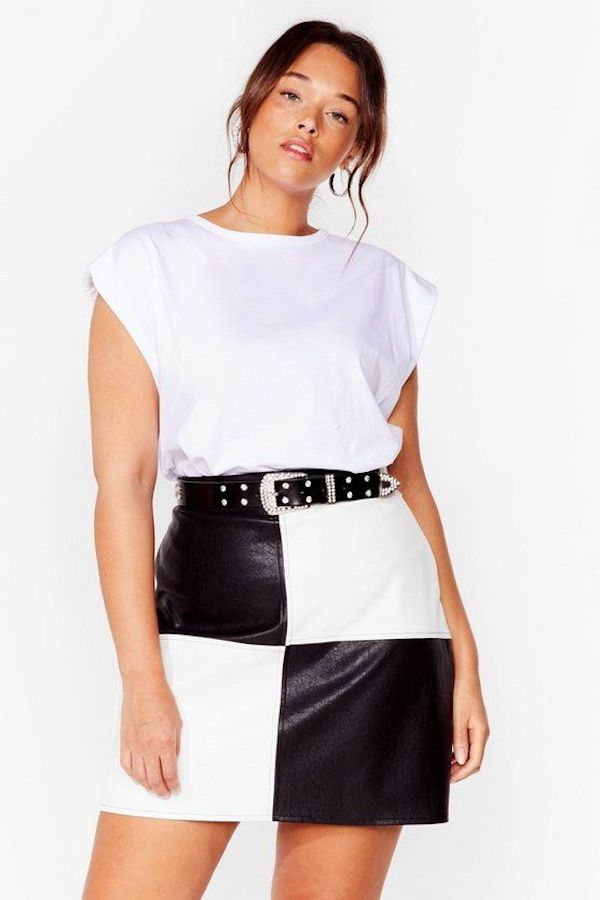A plus-size model wearing a white shoulder pad muscle tee.