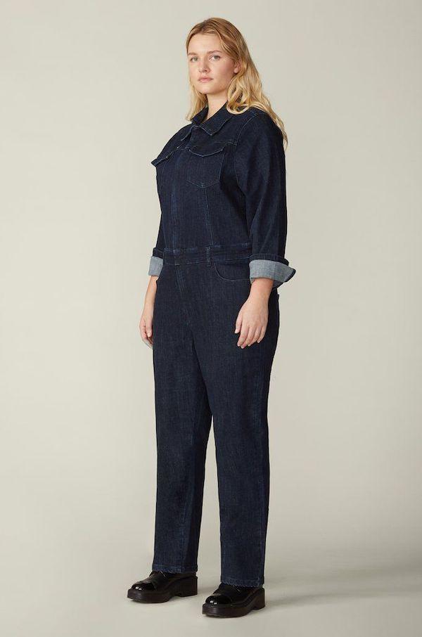 A model wearing a plus-size utility jumpsuit in denim.