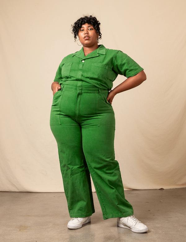 A model wearing a plus-size utility jumpsuit in green.