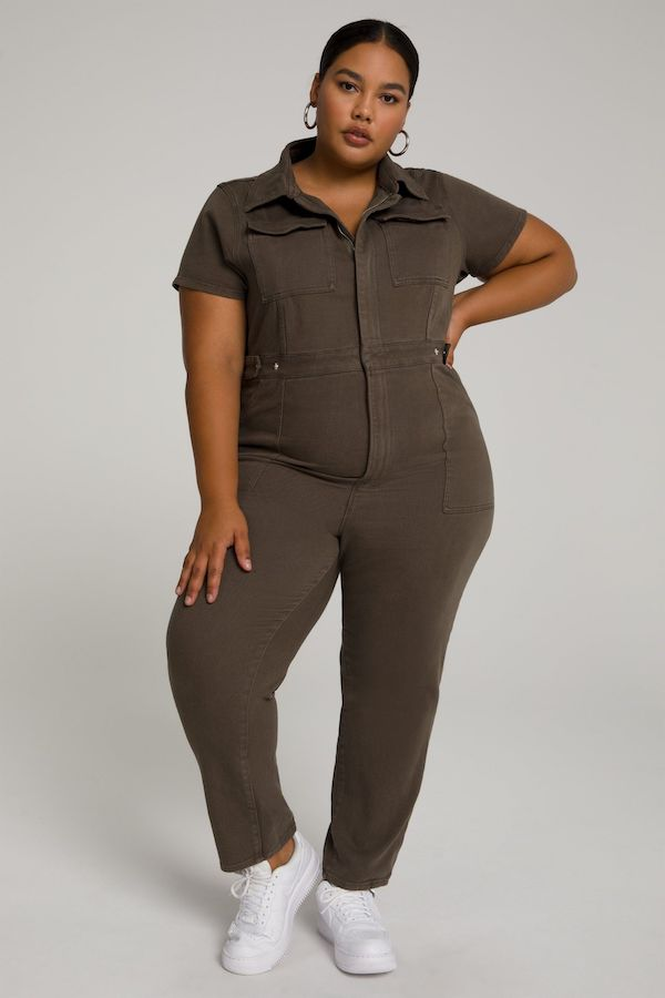 A model wearing a plus-size utility jumpsuit in sage.