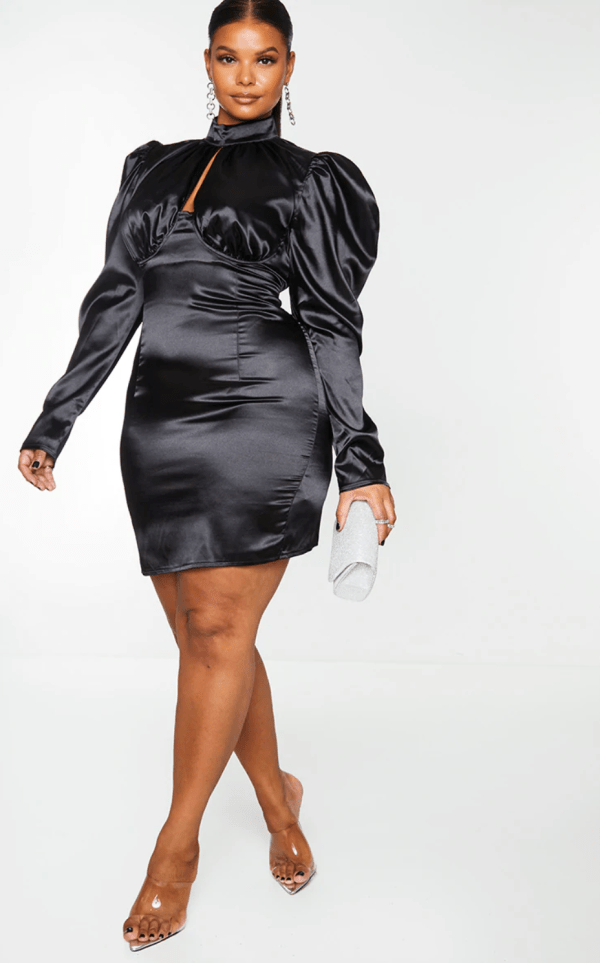 A plus-size model wearing a black ruched satin mini dress.