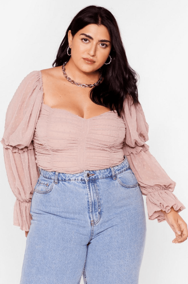 A plus-size model wearing a light pink long-sleeve ruched top.