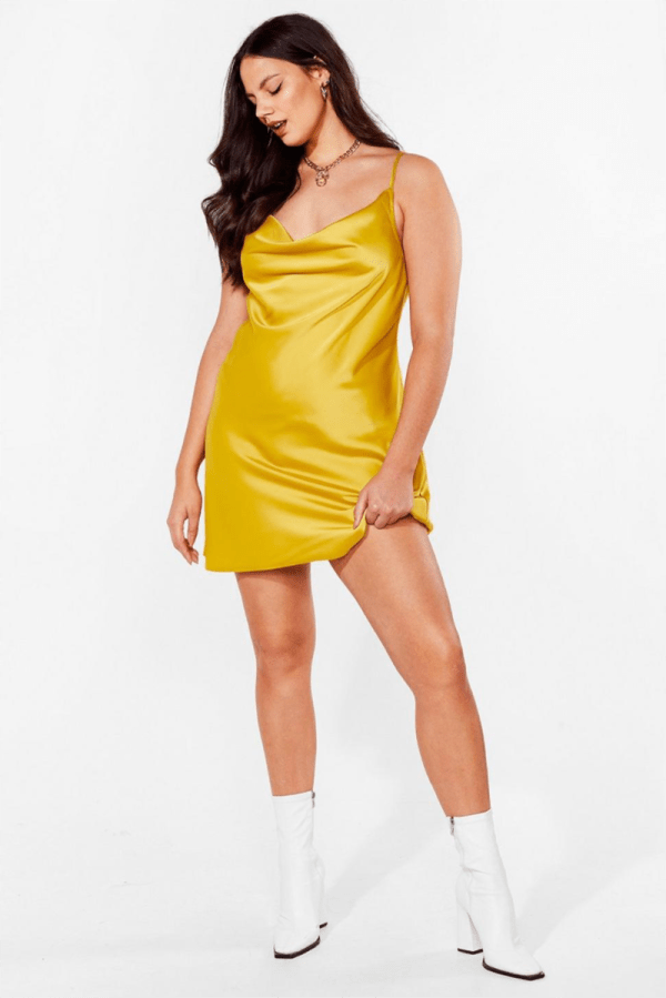 A plus-size model wearing a yellow satin mini slip dress.