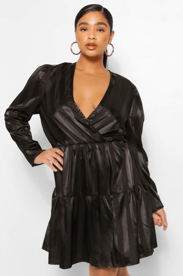 A plus-size model wearing a long-sleeve, black satin mini dress.