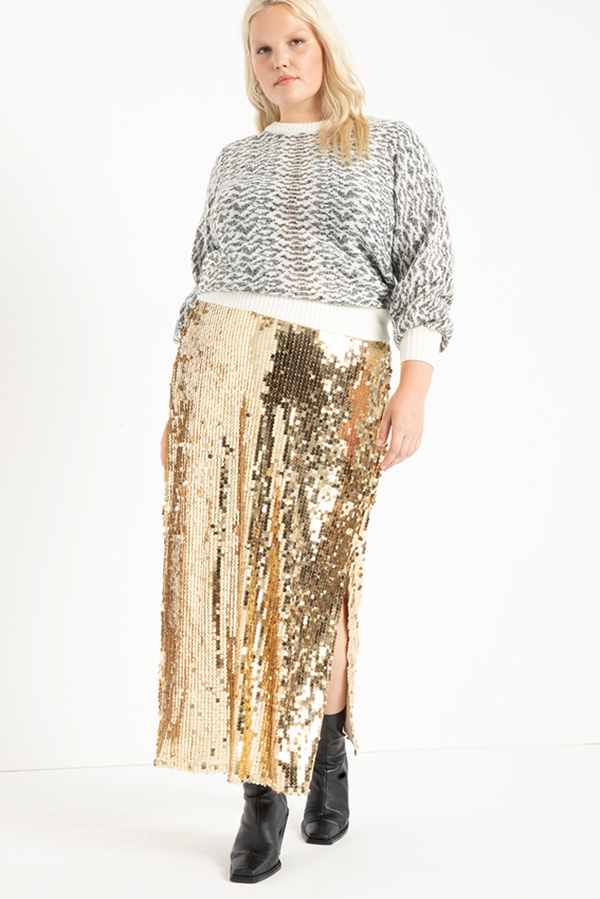 A plus-size model wearing a gold sequin maxi skirt.