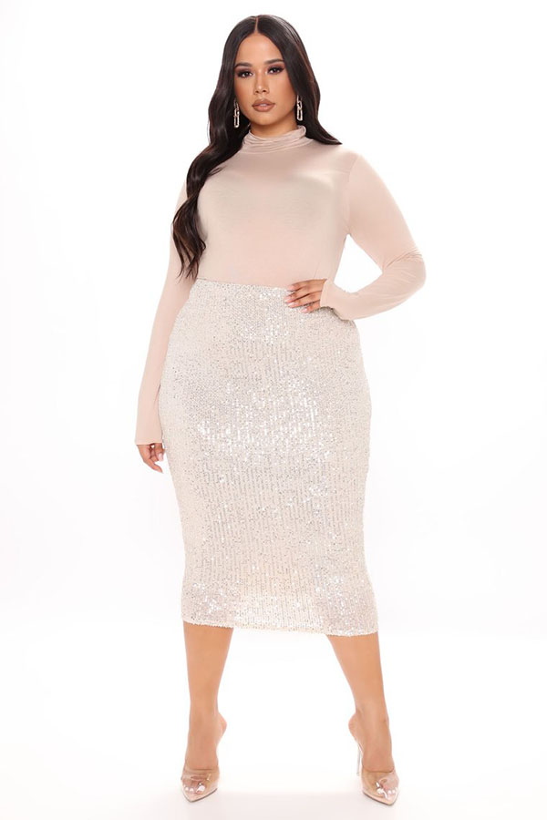 A plus-size model wearing a light pink sequin midi skirt.