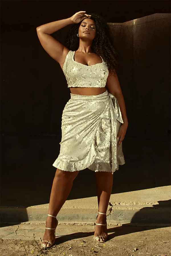 A plus-size model wearing a silver sequin wrap skirt.