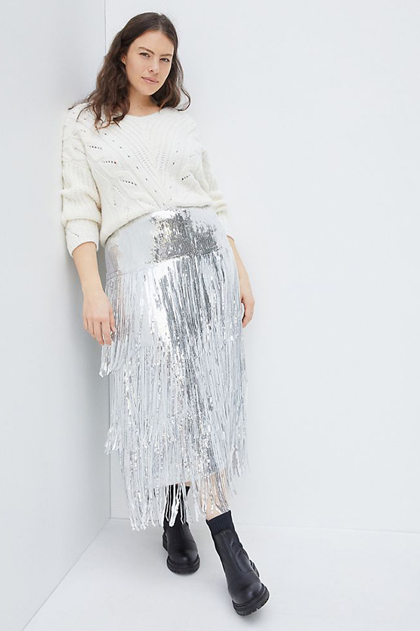 A plus-size model wearing a silver fringe sequin skirt.