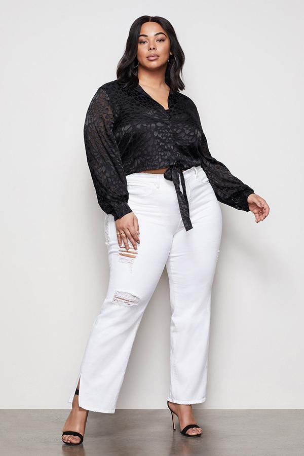 A plus-size model wearing white split-hem jeans.