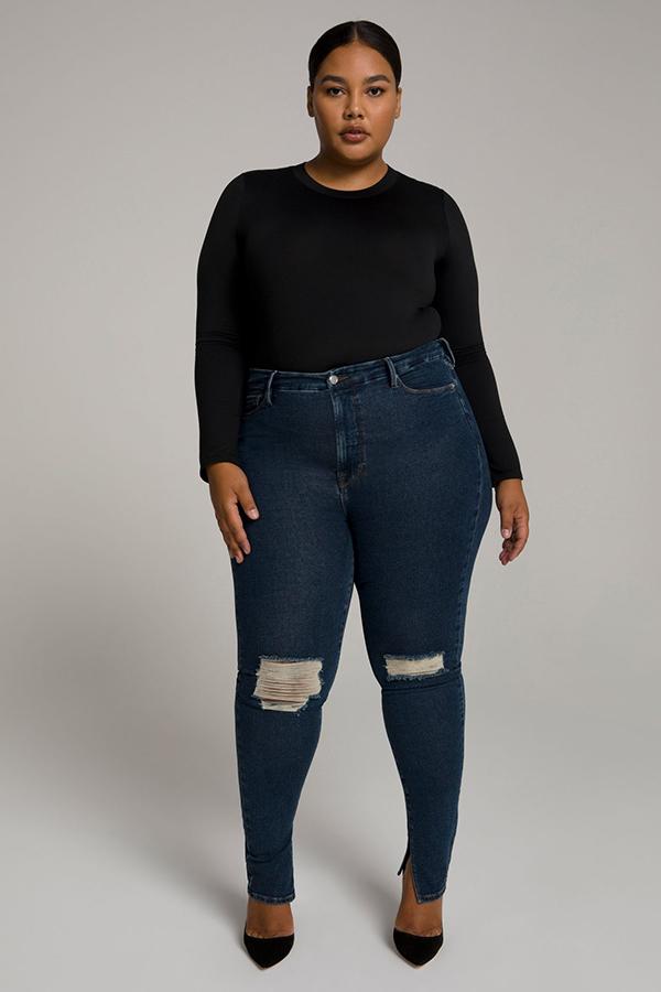 A plus-size model wearing dark-was split-hem ripped skinny jeans.
