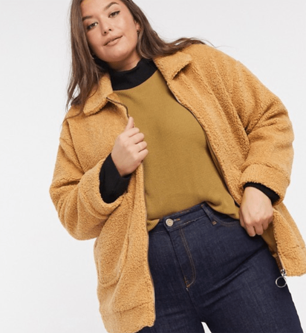 A plus-size model wearing a camel teddy jacket.
