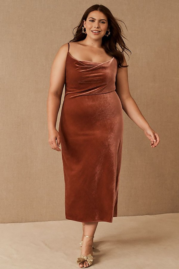 A plus-size model wearing a brown velvet slip dress.