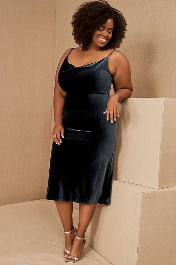 A plus-size model wearing a navy blue velvet slip dress.