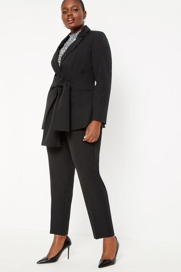A plus-size model wearing a black wrap blazer.