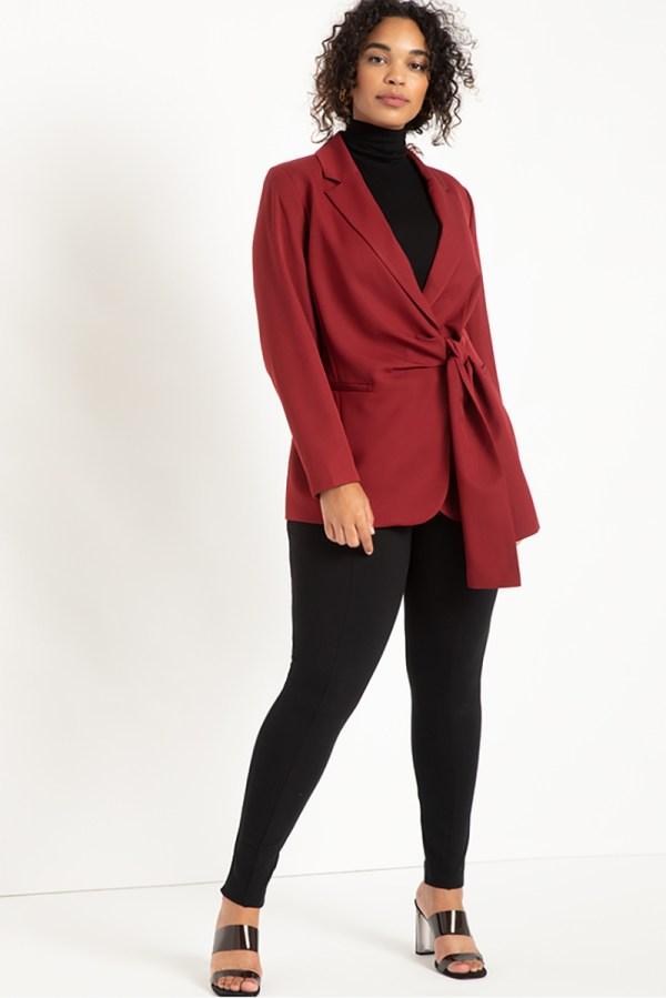 A plus-size model wearing a red wrap blazer.
