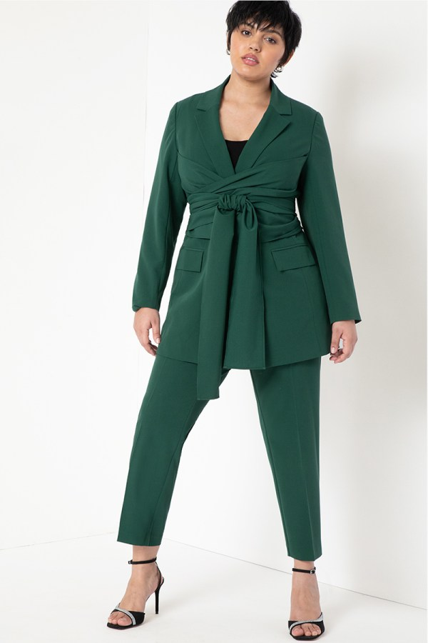 A plus-size model wearing a forest green wrap blazer.