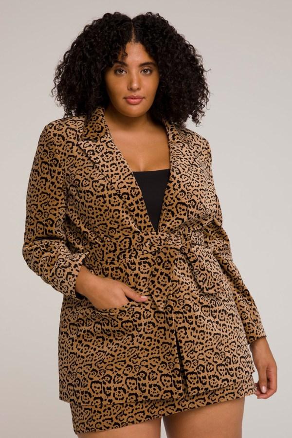 A plus-size model wearing a cheetah print wrap blazer.