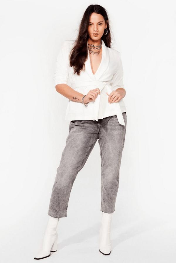 A plus-size model wearing a white wrap blazer.