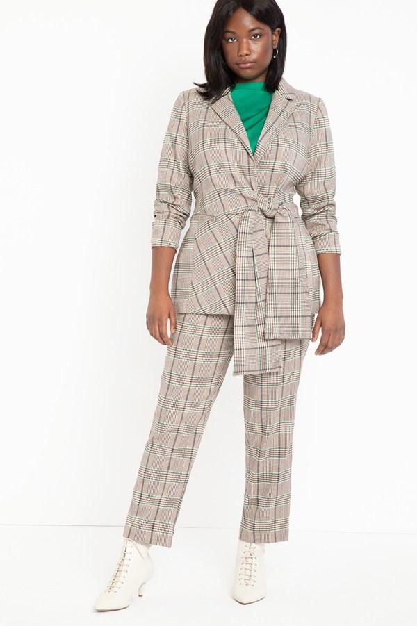 A plus-size model wearing a plaid wrap blazer.