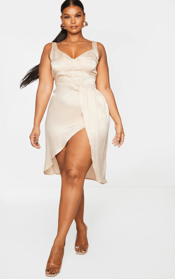A plus-size model wearing a sexy off-white satin dress.