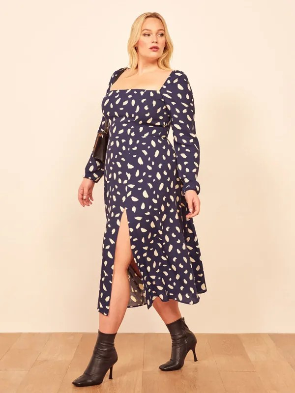 A plus-size model wearing a sexy blue printed dress.