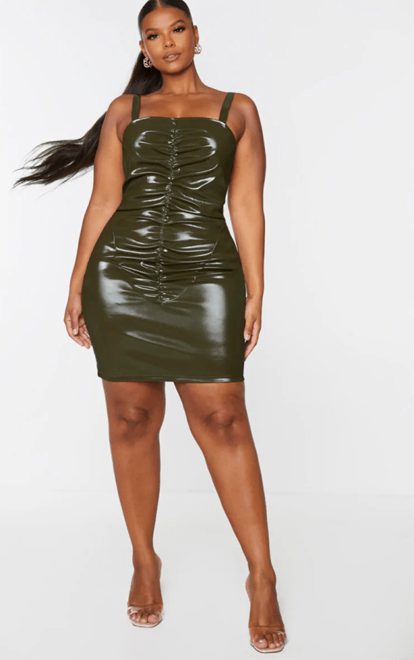 A plus-size model wearing a sexy olive green ruched dress.