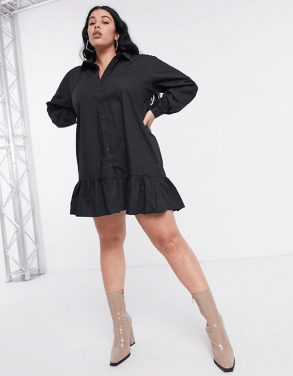 A plus-size model wearing a sexy black smock dress.