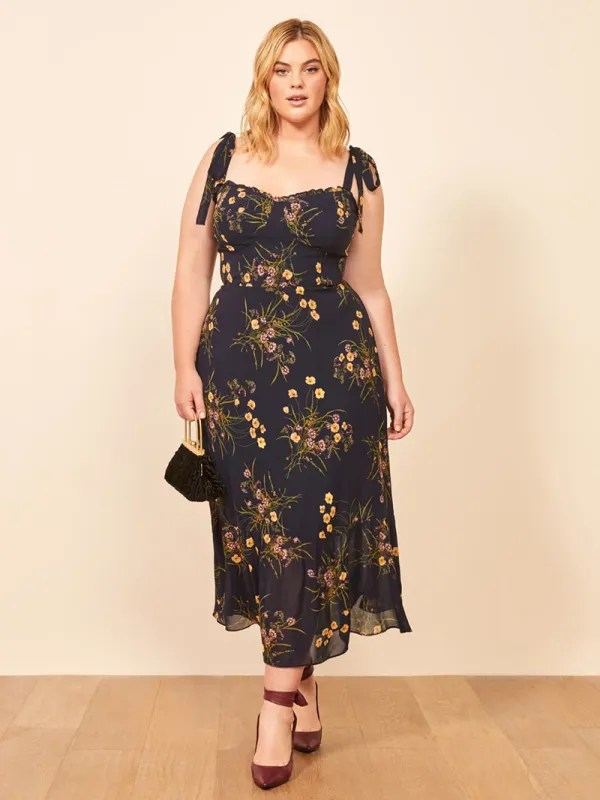 A plus-size model wearing a sexy floral midi dress.