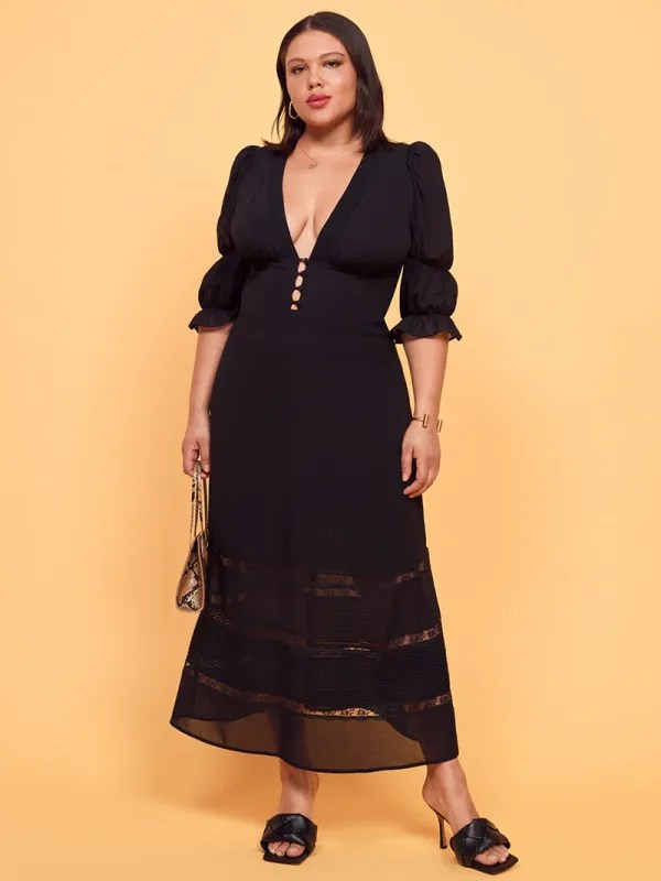 A plus-size model wearing a sexy black dress.