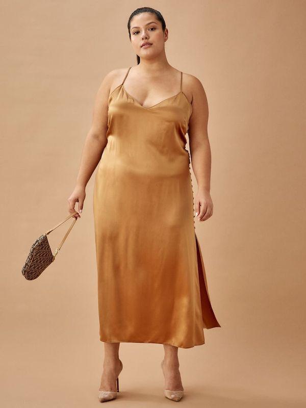 A model wearing a plus-size slip dress in gold.