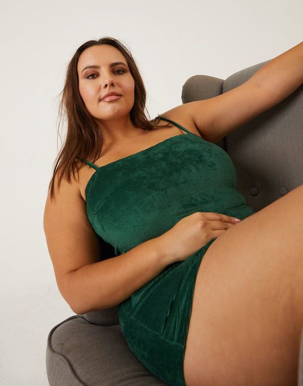 A plus-size model from 2020AVE wearing a green velvet shorts and cami set.