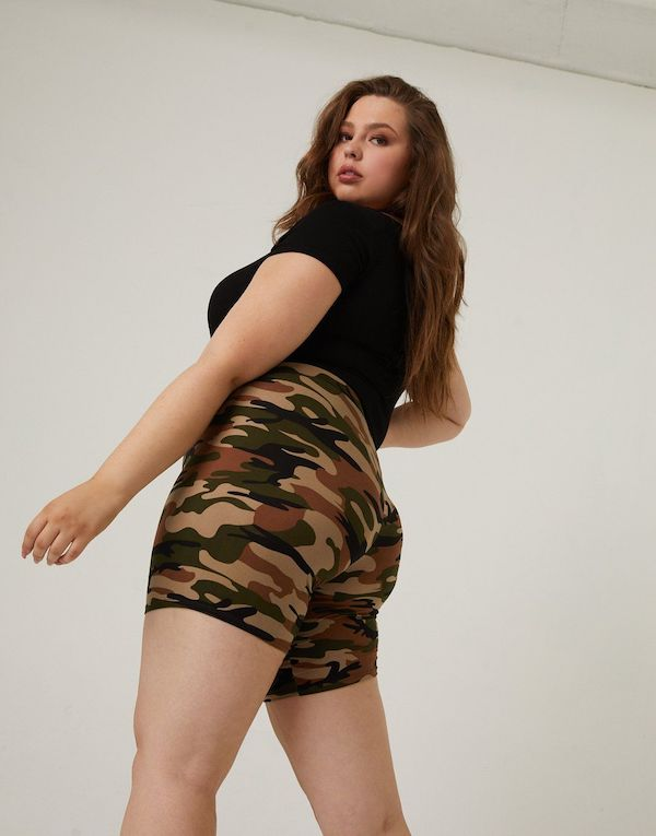 A plus-size model from 2020AVE wearing camo biker shorts.