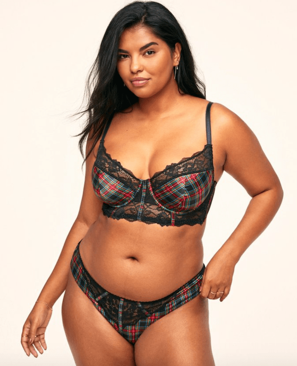 A plus-size model from Adore Me wearing a black and red plaid lingerie set.