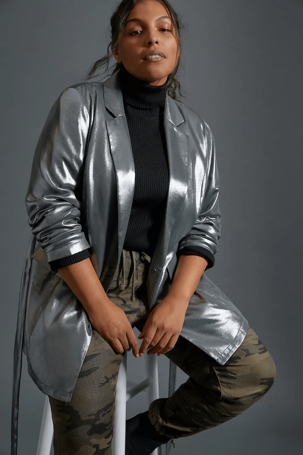 A plus-size model wearing a metallic blazer.