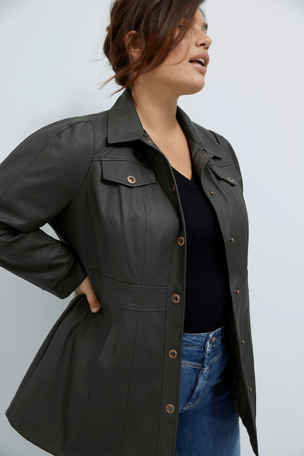 A plus-size model wearing a black leather jacket.