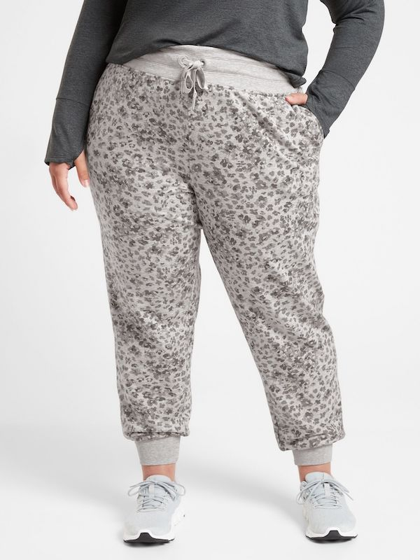 A plus-size model from Athleta wearing gray animal print joggers.