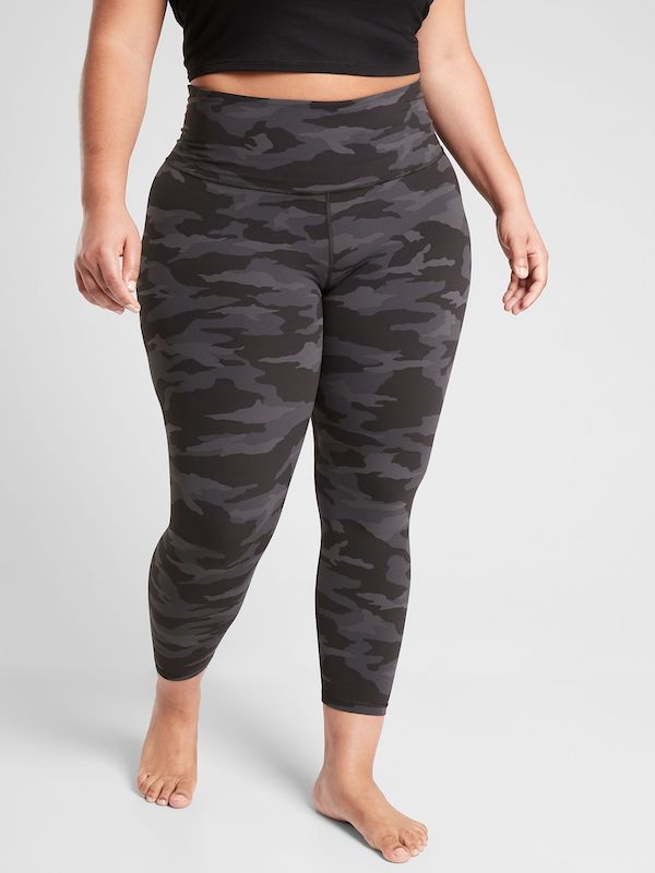 A plus-size model from Athleta wearing black camo leggings.